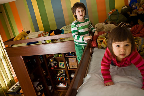 Double loft beds with children playing and under bed storage shelves